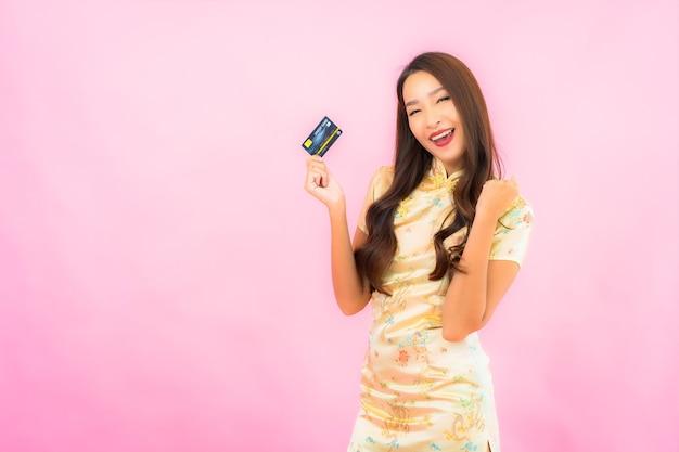 Ritratto bella giovane donna asiatica con carta di credito e telefono cellulare sulla parete di colore rosa