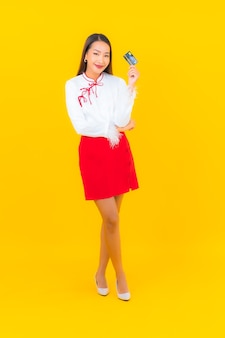 Portrait beautiful young asian woman with credit card for online shopping on yellow