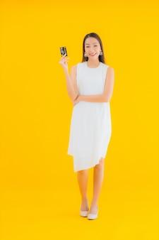 Ritratto bella giovane donna asiatica con carta di credito per lo shopping online
