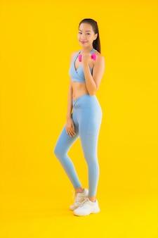 Женщина портрета красивая молодая азиатская с гантелью и sportwear на желтом цвете