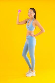Bella giovane donna asiatica del ritratto con la testa di legno e sportwear su giallo