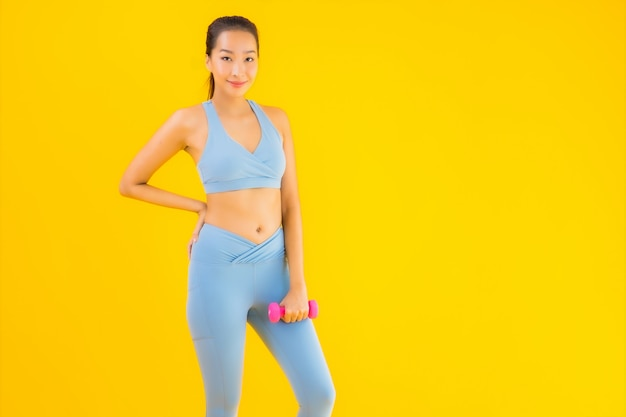 Portrait beautiful young asian woman with dumbbell and sportwear on yellow