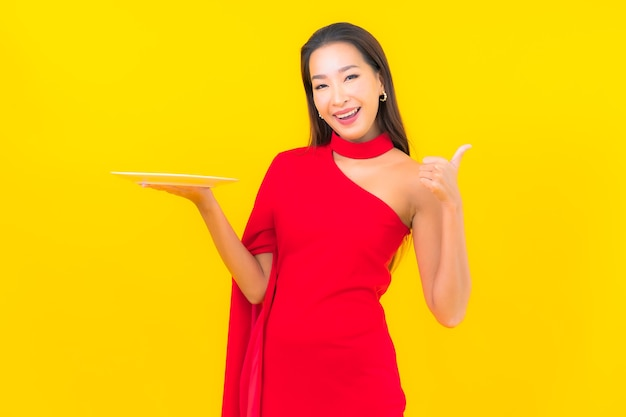 Bella giovane donna asiatica del ritratto con il piatto vuoto del piatto