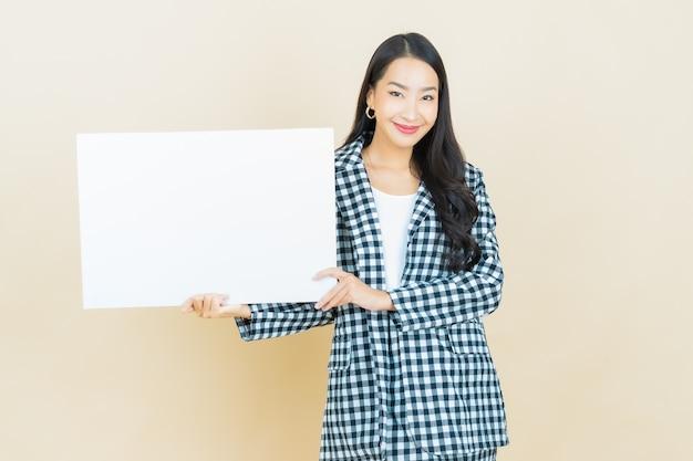 ベージュの空の白い看板を持つ美しい若いアジア女性の肖像画