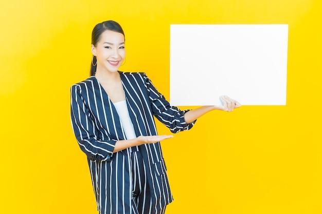 컬러 배경에 빈 흰색 광고판이 있는 아름다운 젊은 아시아 여성의 초상화