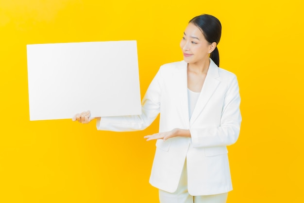 컬러 벽에 빈 흰색 광고판이 있는 아름다운 젊은 아시아 여성 초상화 프리미엄 사진
