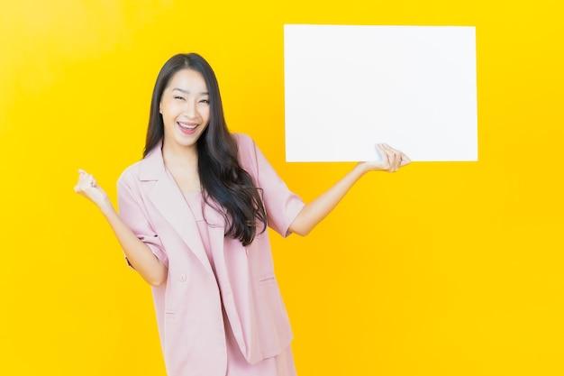노란 벽에 빈 흰색 광고판이 있는 아름다운 젊은 아시아 여성 초상화