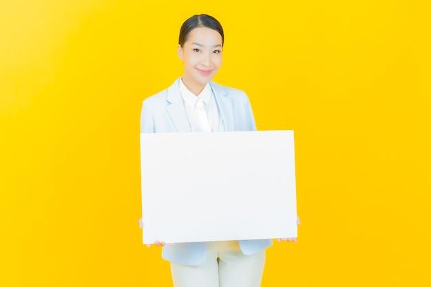 Женщина портрета красивая молодая азиатская с пустой белой афишей на желтом