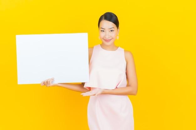 Bella giovane donna asiatica del ritratto con il tabellone per le affissioni bianco vuoto su colore giallo