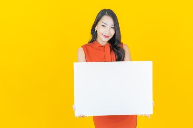 Ritratto bella giovane donna asiatica con cartellone bianco vuoto su yellow