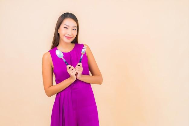 Ritratto bella giovane donna asiatica con forchetta e cucchiaio pronto da mangiare su sfondo colorato