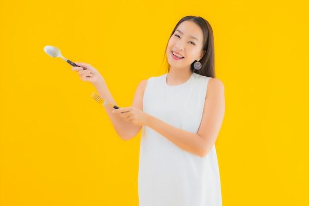 フォークスプーンで美しい若いアジア女性の肖像画