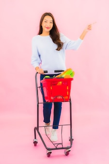 분홍색 격리 된 벽에 바구니에 과일 야채와 식료품 초상화 아름 다운 젊은 아시아 여자