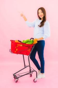Ritratto bella giovane donna asiatica con frutta verdura e merce nel carrello della drogheria sulla parete isolata rosa