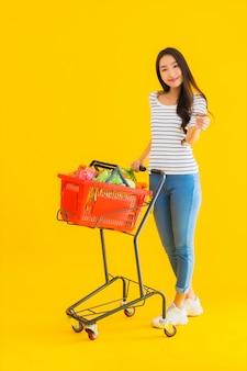 쇼핑몰에서 슈퍼마켓에서 식료품 바구니 카트와 초상화 아름 다운 젊은 아시아 여자