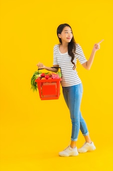 Женщина портрета красивая молодая азиатская с тележкой корзины для товаров от супермаркета в торговом центре