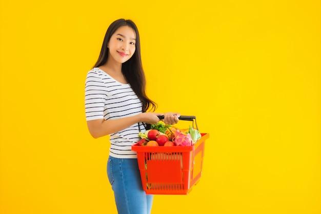 ショッピングモールのスーパーマーケットから食料品の買い物かごを持つ美しい若いアジア女性の肖像画