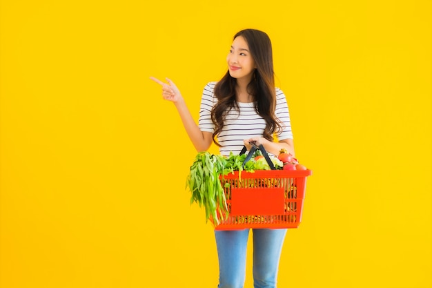 Bella giovane donna asiatica del ritratto con il carretto del canestro della drogheria dal supermercato nel centro commerciale