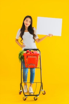 Portrait beautiful young asian woman with grocery basket cart and show white empty board