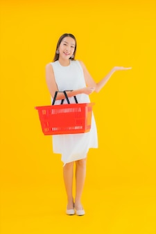 슈퍼마켓에서 쇼핑을위한 식료품 바구니와 세로 아름 다운 젊은 아시아 여자