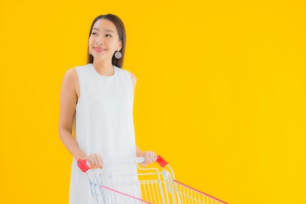 スーパーマーケットからの買い物のための食料品のバスケットを持つ美しい若いアジア女性の肖像画