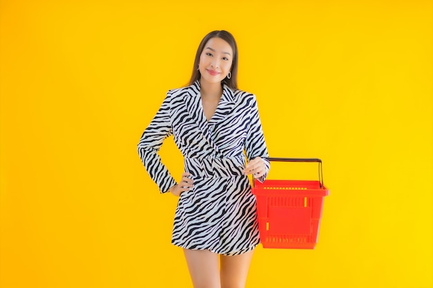 Портрет красивая молодая азиатская женщина с продуктовой корзиной для покупок на желтом