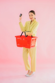 Portrait beautiful young asian woman with grocery basket from supermarket on color
