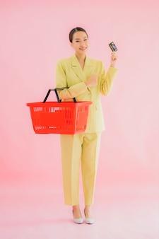 Женщина портрета красивая молодая азиатская с продуктовой корзиной от супермаркета на цвете