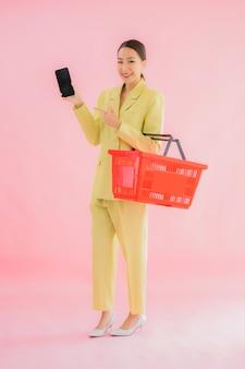 色のスーパーマーケットから食料品のバスケットを持つ美しい若いアジア女性の肖像画