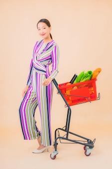 色のスーパーマーケットからの食料品バスケットを持つ肖像画の美しい若いアジアの女性