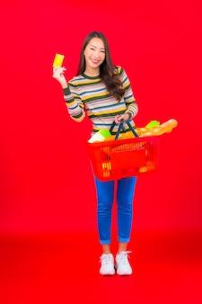 赤い孤立した壁にスーパーマーケットから食料品バスケットを持つ肖像画美しい若いアジアの女性