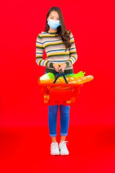 빨간색 격리 된 벽에 슈퍼마켓에서 식료품 바구니와 세로 아름 다운 젊은 아시아 여자