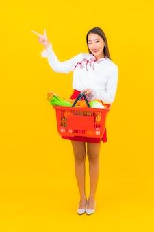 黄色のスーパー マーケットからの食料品のバスケットを持つ美しい若いアジアの女性の肖像画