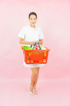 Portrait beautiful young asian woman with grocery basket from supermarket on pink wall
