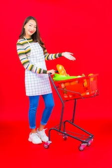 Bella giovane donna asiatica del ritratto con il cestino della drogheria dal supermercato sulla parete isolata rossa