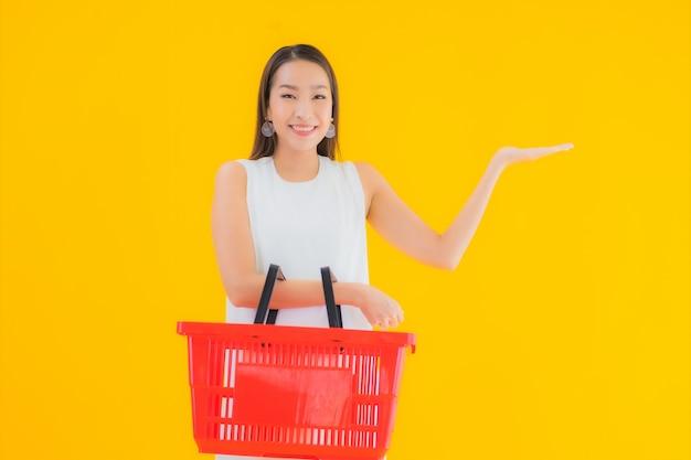 Bella giovane donna asiatica del ritratto con il cestino della drogheria per fare la spesa dal supermercato