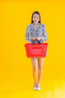 Portrait beautiful young asian woman with grocery basket for shopping on yellow