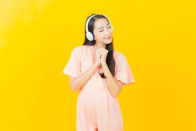 노란 벽에 음악을 듣기 위해 헤드폰과 스마트 폰을 가진 아름다운 젊은 아시아 여성의 초상화