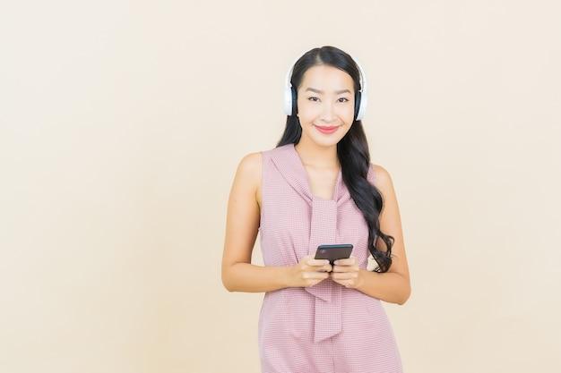 音楽を聴くためのヘッドフォンとスマートフォンを持つ肖像画の美しい若いアジアの女性