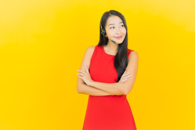 Portrait beautiful young asian woman with headset for communication and support call center service on yellow wall