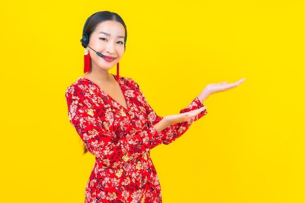 Ritratto bella giovane donna asiatica con auricolare per la cura del call center del cliente sulla parete gialla