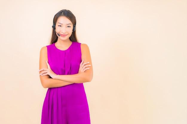色の背景にコールセンターの顧客のためのヘッドセットを持つ肖像画の美しい若いアジアの女性