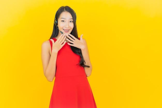 黄色の壁に通信とサポートのコールセンターサービスのためのヘッドセットを持つ肖像画の美しい若いアジアの女性
