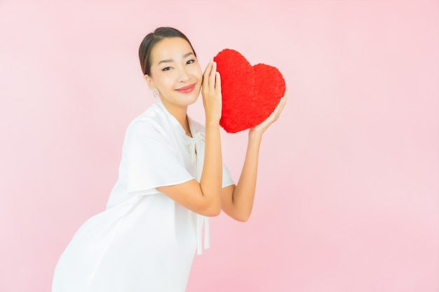 Portrait beautiful young asian woman with heart pillow shape on pink wall