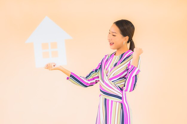 Portrait beautiful young asian woman with home or house sign paper on color