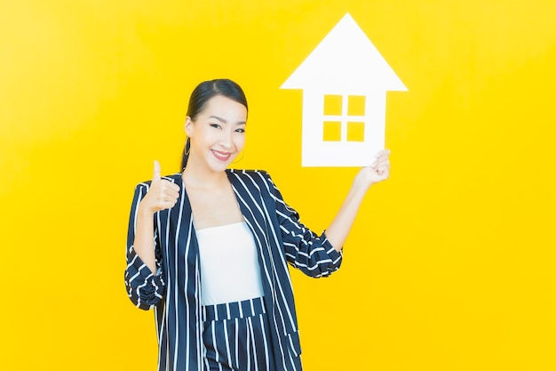 Portrait beautiful young asian woman with house or home paper sign on color background