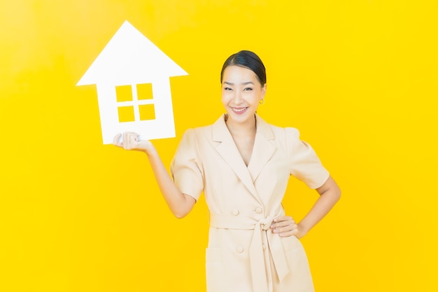Portrait beautiful young asian woman with house or home paper sign on color wall