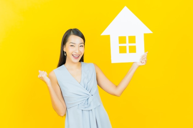 Portrait beautiful young asian woman with house or home paper sign