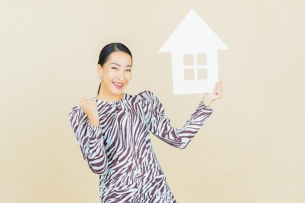 Женщина портрета красивая молодая азиатская с домом или домашним бумажным знаком на бежевом