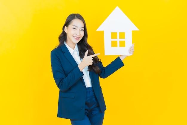 노란색에 집이나 집 종이 표지판이 있는 아름다운 젊은 아시아 여성 초상화
